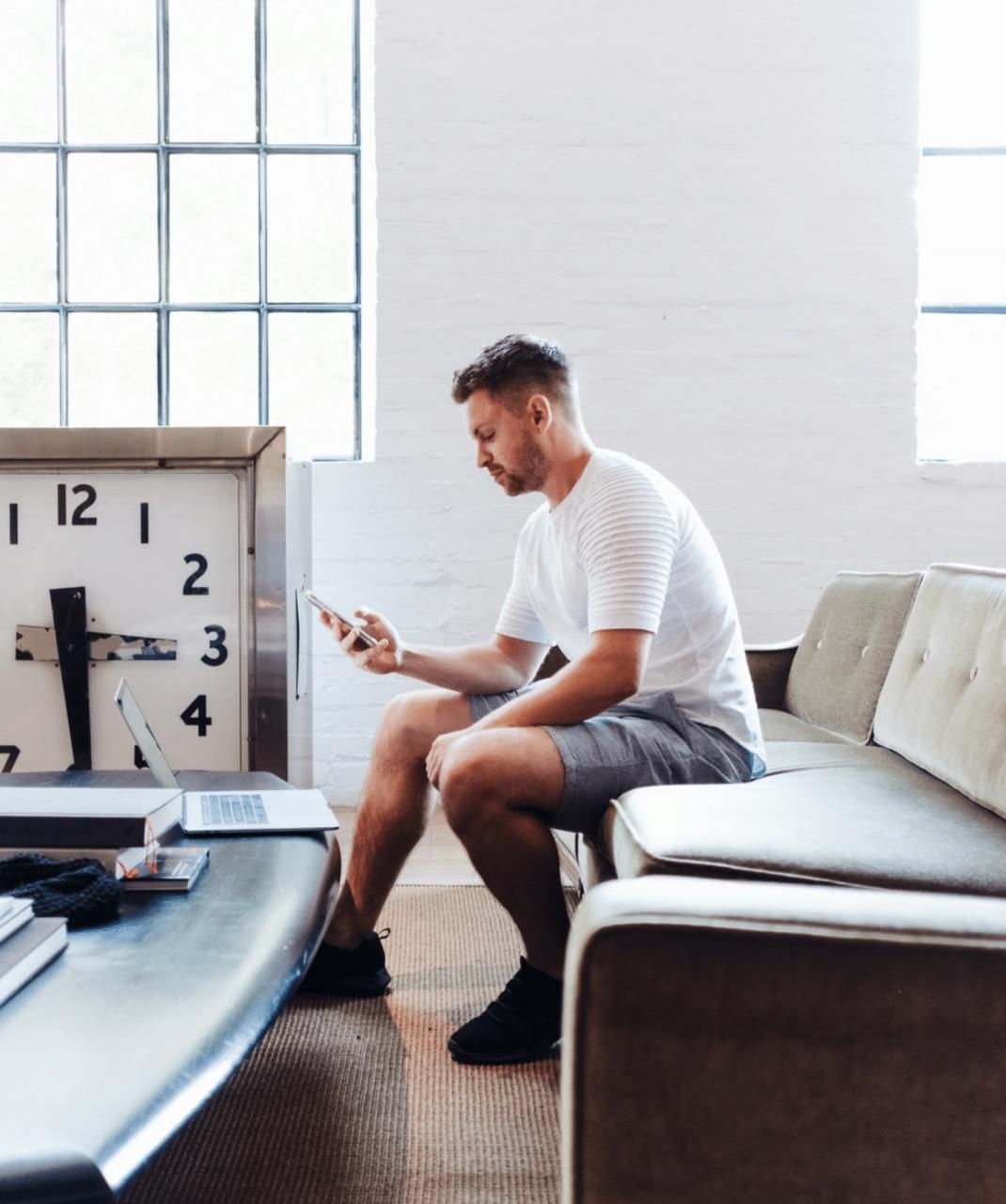 Man sitter i en soffa och skriver chattmeddelande på telefon