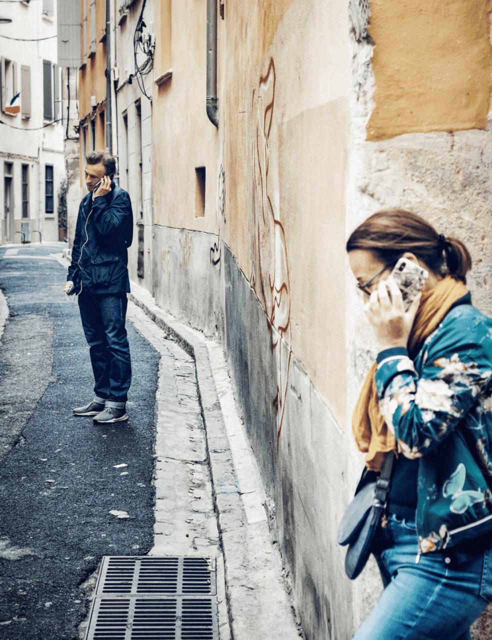 En kvinna och en man är i varsitt telefonsamtal i en gränd