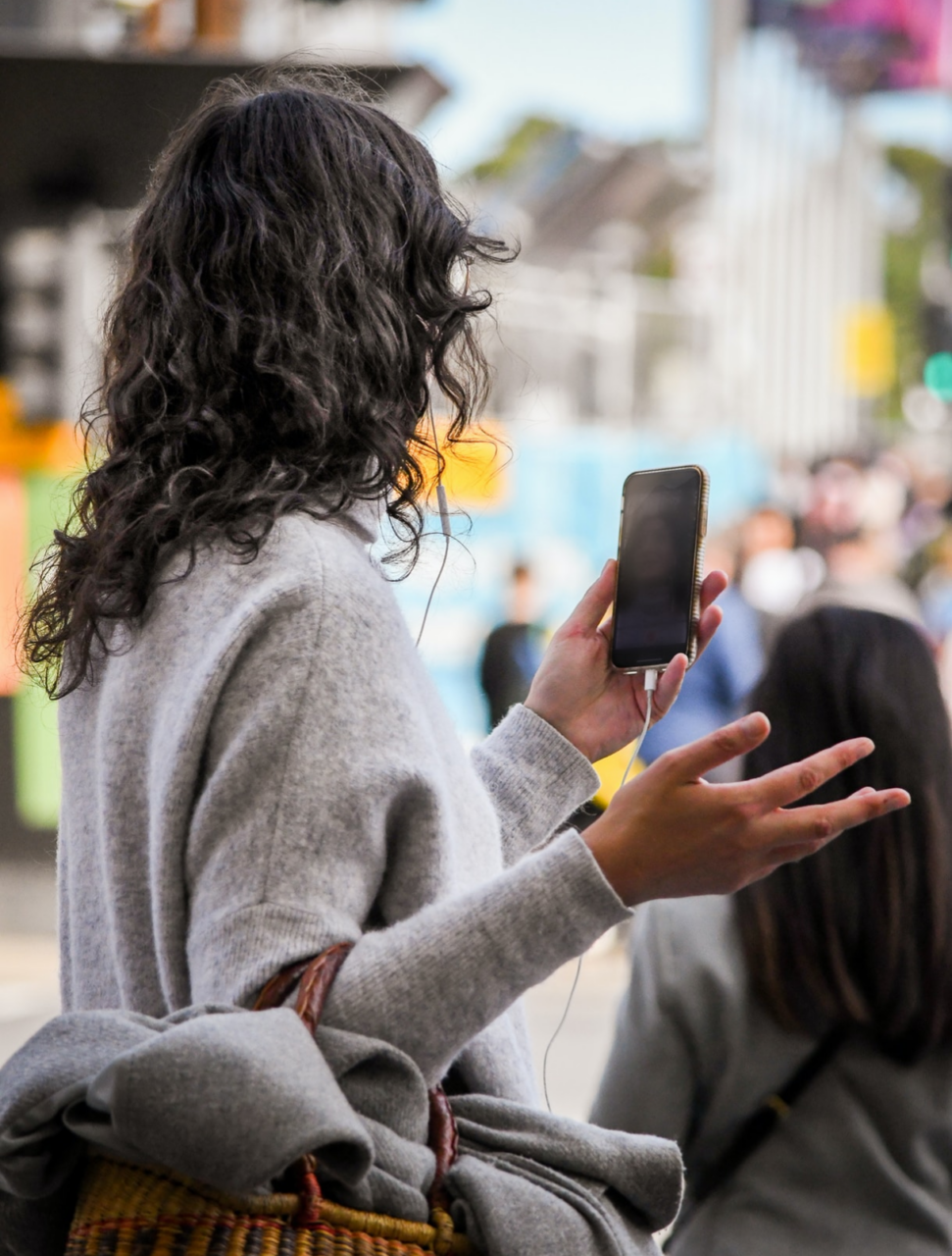 Woman using video call function while walking on the street