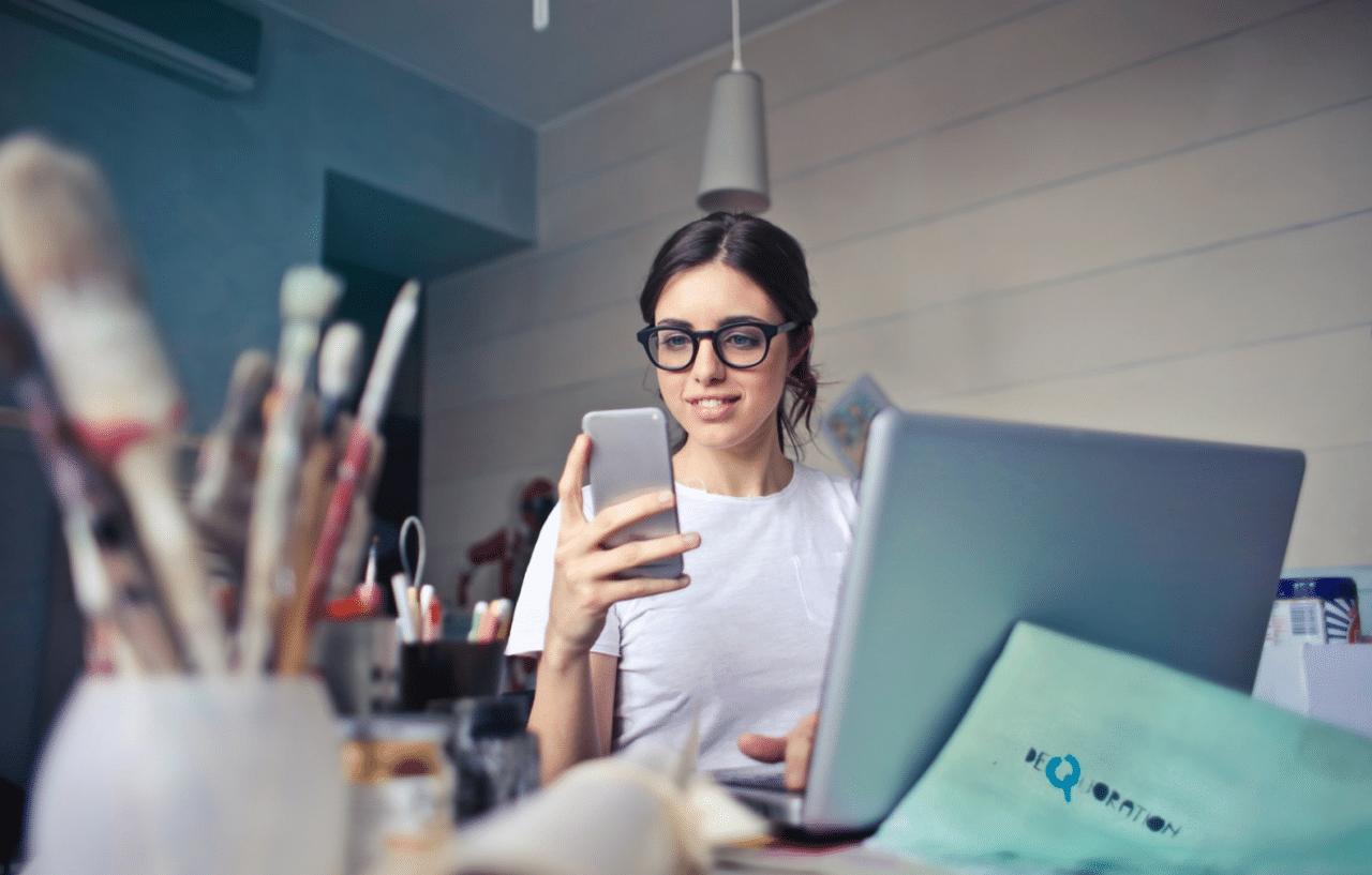 Ung kvinna använder sociala medier på mobil och dator samtidigt